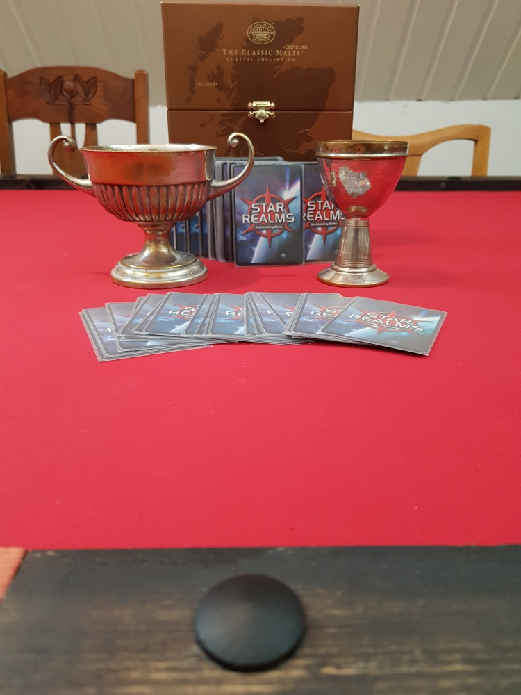 The cups of the competition with star realms cards around them
